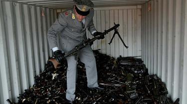En italiensk toldbetjent undersøger en container med cirka 8.000 maskingeværer fra Rumænien, der blev beslaglagt   i havnebyen Gioia Tauro.
