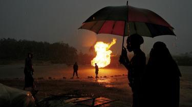 En kvinde har fundet ly fra regnen under en paraply, mens en naturgaskilde brænder bag hende i Niger-Delta, Nigeria.