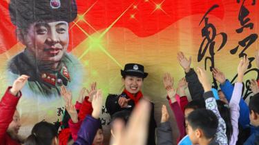 For også at begejstre en ny generation af kinesere har kommunistpartiet endnu engang pustet liv i ikonet Lei Feng, der med et varmt smil opfordrer folket til at være gode samaritanere og udvise kærlighed til partiet. Her er det skoleelever i Shenyang, der lytter til historier om den berømte soldat som forberedelse til den årlige Lei Feng-dag.