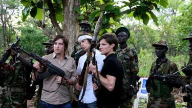 Invisible Childrens tre grundlæggere Bobby Bailey, Laren Poole og Jason Russell poserer med rifler sammen med medlemmer af Sudan People's Liberation Army (SPLA), som har kæmpet mod LRA.