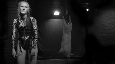 Cecilie Ullerup Schmidt fortalte omhyggeligt om forskellige former for svinebrug, mens hun havde hængt sig selv op i en krop, så hun for et øjeblik delte skæbne med svinet bagved, i Café Teatrets Projekt Landbrug.