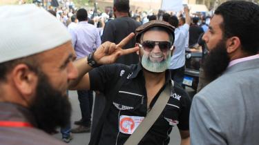 En egyptisk tilhænger af Det Muslimske Broderskab viser sejrstegnet, mens han bærer en maske med ansigtet af de islamiske salafisters præsidentkandidat, Hazem Abu Ismail. En stor protest fandt sted uden for statsrådsdomstolen, da denne suspenderede de islamiske kræfters udkast til en ny forfatning, som boykottes af liberale borgere, moderate muslimer og de koptiske kristne.