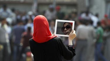 En ung egyptisk kvinde bruger sin tablet til at videofilme demonstranter på Tahrir -pladsen midt i Kairo. I går var der store protester mod den i mange egypteres øjne milde livstidsdom til den 84-årige Mubarak for hans 31 år lange regime og hans ansvar for drab på over 800 borgere i januar sidste år under revolutionen midt i hovedstaden.