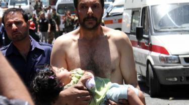 En syrisk mand bærer en såret pige efter en eksplosion mod en militærbus i Qudssaya – et kvarter i hovedstaden Damaskus. I går afholdt Information debatmøde om spørgsmålet: Skal Vesten intervenere i Syrien?