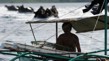 En filippinsk fisker i sin båd, mens hærens frømand og amerikanske soldater i gummibåde under en øvelse racer mod Palawan-øen.