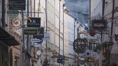 Typiske smedejernsskilte i Getreidegasse, der er Salzburgs pæne forretningsgade. En verden til forskel fra bogens kælderbutik i det mindre pæne Scherzhauserfeld-kvarter .
