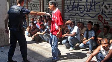 Græske betjente tilbageholder en gruppe indvandrere i det centrale Athen den 5. august. På nuværende tidspunkt er mere end 2.000 indvandrere interneret.