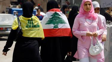 Libanesiske kvinder i en af Beiruts sydlige forstæder, hvoraf den ene (tv.) bærer Hizbollahs gule flag med 'Guds Parti' skrevet med grønt over skuldrene, mens den anden bærer det libanesiske flag med cedertræet. De sydlige forstæder er tæt befolket og styret af Hizbollah, og blev til dels derfor bombet heftigt i sommeren 2006 af Israel.