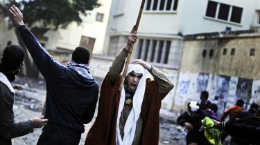 Bag facaden. 'Folket og hæren er én hånd,' råbte demonstranter på Tahrirpladsen under oprøret, der væltede Mubarak. Men i dag spørger mange sig selv, om de snarere var nyttige idioter for et militærkup til gavn for islamisterne. Her støder demonstranter sammen med sikkerhedsstyrker på Tahrirpladsen  i november 2011.