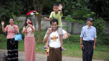 Lokale indbyggere i Yangon i Myanmar står klar med flag for at hilse på Obama, der er den første amerikanske præsident, som har besøgt landet.