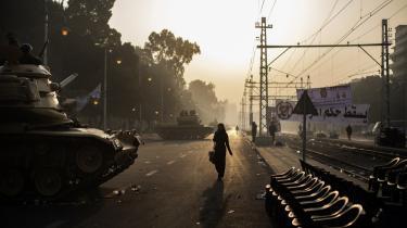 Opstilling. Et morgensøvnigt Kairo passerer forbi militærets opstilling foran præsidentpaladset. Den er ikke så meget for at beskytte præsident Morsis person som for at vise respekt for præsidenten som institution, vurderer iagttagere.