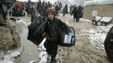 En afghansk dreng slæber glad nødhjælpspakker fra EU og UNHCR, der skal forsøde livet i den kolde afghanske vinter for ham og hans familie, der bor i en flygtningelejr i Kabul.
