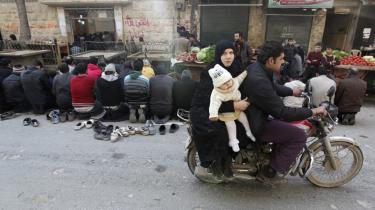 Ingen nødhjælpsorganisationer kan overskue mængden af ngo'er, der arbejder i Syrien. Mange er improviserede, opstår hurtigt og forsvinder igen. Her beder mænd på gaden i Aleppo  i går, mens en familie kører forbi på knallert.