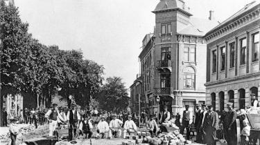 Hernings hovedgade blev brolagt for første gang i sommeren 1903. Brolæggerne er her fotograferet på Torvet foran Hotel Eyde. Foto: Danmarksbilleder.dk