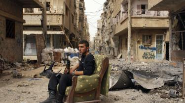 Et medlem af Den Frie Syriske Hær sidder på en sofa midt i en gade i Deir al-Zor. USA mener, der er håndfaste beviser for, at regimet i Syrien har brugt kemiske våben. Derfor vil amerikanerne sende våben til den syriske opposition.