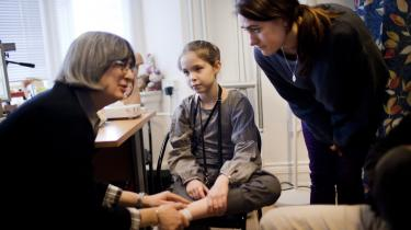 En pige er med sin mor hos familiens praktiserende læge (tv.) med sin dårlige fod.