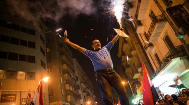 En demonstrant står på taget af en bil og fejrer, at Mohamed Mursi er afsat som præsident. Efter fire dages protester brød militæret ind.