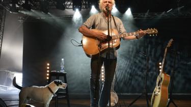 Allan Olsen kender ikke overklassen og akademikerne, så derfor indgår deres liv ikke i hans tekster. Her står han på scenen med terrier og guitar ved Bork Havn.