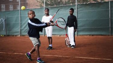 Yalol og Londo Kamara ser til, mens seksårige Fidel Dennis sender sin dobbelte baghånd af sted. Hans yndlingsslag er forhånd og slice, og han tror, John Isner vinder US Open.