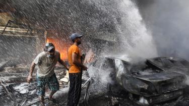 Hizbollah-støtter forsøger at slukke en ildebrand efter en bilbombe er eksploderet ved en Hizbollah-højborg i en forstad til Beirut.