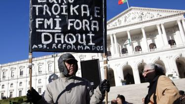 En portugisisk pensionist demonstrerer mod EU og Trojkaen foran parlamentsbygningen i Lissabon.