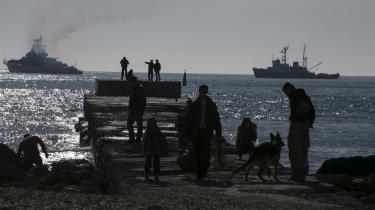 Folk iagttager russiske skibe, der blokerer Donuzlav Bay, hvor tre ukrainske skibe har nægtet at overgive sig. De ukrainske styrker på Krim føler, de er blevet ladt i stikken af ledelsen i Kijev.