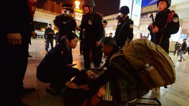 Kinesisk politi hjælper en kvinde efter et terrorangreb i Kunming 2. marts, hvor 29 døde. Stemningen er anspændt mellem hankineserne og de lokale uighurer, der føler sig udstødt af det kinesiske jobmarked