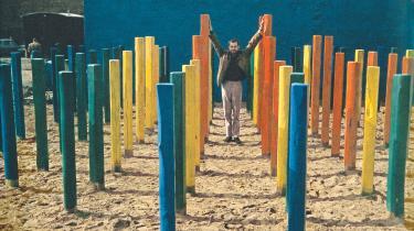 Kasper Heiberg midt i sit værk 'Miljø' (1967), en lille skov af groft huggede pæle i forskellige farver og højder anbragt som en gennemskuelig labyrint op ad en dybblå væg på en ubebygget grund i Århus. Foto fra bogen