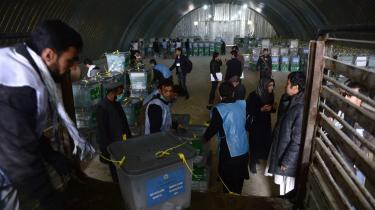 Afghanske valgtilforordnede læsser stemmebokse af en lastbil i et lager i Kabul. Men selvom valget tyder godt, går der flere uger, før et klart billede tegner sig.