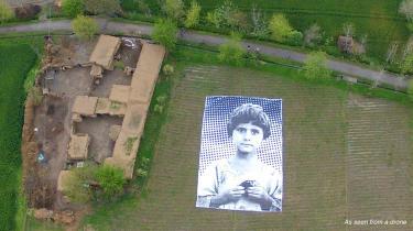 Kunstnergruppen #NotABugSplat har placeret en enorm plakat med et billede af en pakistansk pige på en mark i det nordvestlige Pakistan.