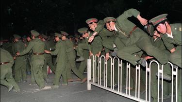 Soldater springer over barrieren for at rydde Den Himmelske Freds Plads for demonstranter 3-4. juni 1989. Ingen ved, hvor mange der blev dræbt, da demonstrationerne blev slået ned, og i dag er protesten i det hele taget et sort hul i kinesisk historie.
