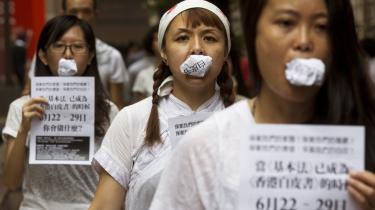 Lokale kunstnere har puttet fotokopier af 'ét land, to systemer'-modellen i munden for at protestere over, at Hongkongs borgeres ytringsfrihed er blevet forringet. Utilfredsheden stiger blandt beboerne i millionbyen, fordi de mener, deres frihedsrettigheder presses fra Beijing.
