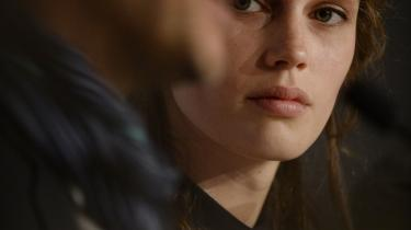 Den franske skuespiller Marine Vacth kigger på instruktør François Ozon under en pressekonference. I filmen 'Ung & smuk' vises den unge kvinde i sin ret til at administrere sit begær, som hun vil.