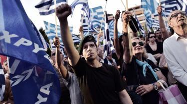 En tilhænger af det græske ultranationalistiske parti Gyldent Daggry løfter armen unden en protest i Athen i maj i år.