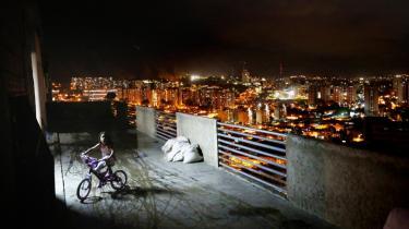 En pige cykler en tur på en altan i det forladte højhus Torre David i Caracas. Det konkursramte prestigebyggeri bliver nu rømmet for bz'ere, der har omdannet bygningen til et lodret slumkvarter.