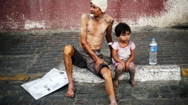 To sårede palæstinensere venter på behandling foran hospitalet i Khan Younis i Gaza-striben.