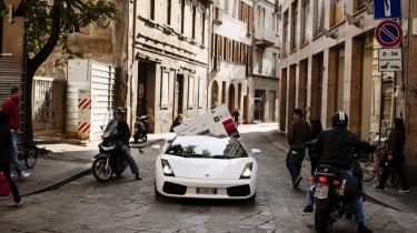 En 46-tommers fladskærm titter frem fra bagsædet af en hvid Lamborghini. Det frie marked har udspillet sin rolle i samfundsøkonomien, skriver Preben Wilhjelm i sin selvbiografi 'Man kan sagtens være bagklog'.