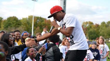 Rapperen Flame hilser på fans ved arrangementet 'Hope for Ferguson'. Den amerikanske by har siden starten af august været centrum for protest, fordi en 18-årig blev skudt og dræbt af politiet. Rappere har igennem årtier fortalt om et klassedelt samfund, hvor en enkelt gnist kunne få alt til at eksplodere.