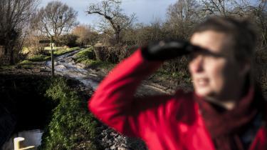 Clare Aparicio viser det sted, hvor planen er at bygge en jorddæmning til forsvar mod fremtidige oversvømmelser. Dæmningen skal gå hele vejen rundt om landsbyen, og beboerne har selv samlet ind til den.