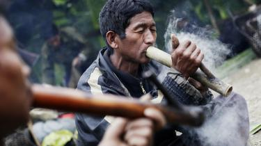 Et par myanmarske mænd ryger opium fra traditionelle bambuspiber under en jagttur i Naga-området i det nordvestlige Myanmar. Mange unge mænd og ældre ryger og dyrker opium, da det giver gode penge, som de kan købe tøj og husholdningsartikler for. Kvinder i dette område i Myanmar ryger sjældent opium.