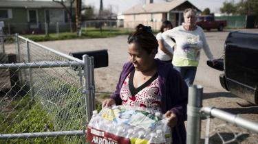 Donna Johnson – i baggrunden – bringer vand ud i byen. Nødløsninger med distribution af drikkevand i flasker og opstilling af vandtanke til brugsvand breder sig i. Det samme gør fornemmelsen af, at det kun er en stakket frist.