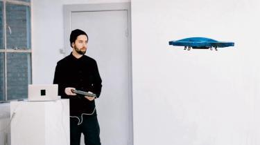 Jacob Sikker Remin styrer en lille legetøjsdrone af Parrot AR 2.0-typen rundt i udstillingens katastrofearkitektur, som i denne enkeltstående anledning fungerer som scenografi.
