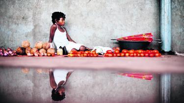 Mozambique. I et lille vejkryds i udkanten af Chokwe sidder en ung pige og sælger kokosnødder og tomater, mens hun passer sin lillesøster. Det er almindeligt i Mozambique, at de større piger passer deres mindre søskende, hvis de ikke hjælper til i marken, hvilket desværre går ud over skolegangen. Mange mænd rejser væk som migrantarbejdere til guldminerne i Zimbabwe og Sydafrika, så ofte er det kvinderne, børnene og de ældre, der sørger for markerne og husholdningen derhjemme. Mændene kommer kun hjem på ferie en-to gange om året.