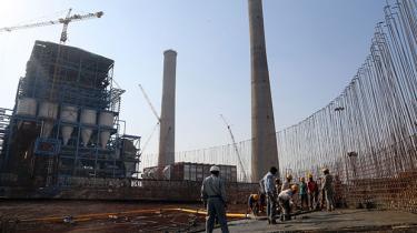 Arbejdere støber en betonkonstruktion under et nyt kulkraftværk iKudgi , Indien.