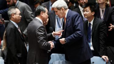 Den kinesiske udenrigsminister Wang Yi taler med sin amerikanske kollega inden mødet i FN's Sikkerhedsråd om Syrien. Sikkerhedsrådet vedtog fredag en resolution, der sigter på at slutte krigen i Syrien gennem fredsforhandlinger.