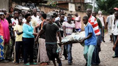 Mænd bærer et lig i Burundis hovedstad Bujumbura i december. Der er flere dræbte i den politiske vold i landet, og eksperter frygter, at det kan udvikle sig til en regulær borgerkrig.