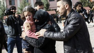 En syrisk kvinde med et såret barn på armen får hjælp til at komme frem til et tyrkisk hospital i Kilis. Syd for grænsen i A'zaz blev et hospital bombet i går.