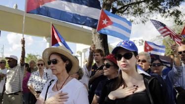 Cubansk-amerikanere rejser sig for både den cubanske og amerikanske nationalhymne under en demonstration mod præsident Obamas Cuba-politik i Miami-kvarteret Little Havana.
