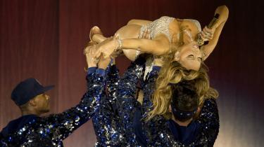 Som en ironisk kommentar til det faktum, at hun ikke står på skuldrene af nogen branchebagmænd, lader Mariah Carey sig bære ind på scenen i vandret position af sine anonyme mandlige dansere.