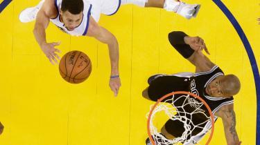 Stephen Curry i hvidt lægger an til at score, mens San Antonio Spurs' David West må se magtesløst til. NBA-kamp tidligere på måneden.